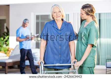 Female nurse assisting senior woman to walk with Zimmer frame at nursing home - stock photo