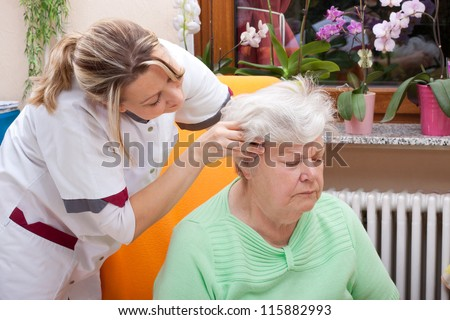 female Nurse massages the head of a senior - stock photo