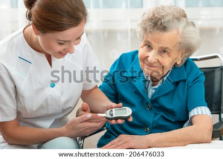 Female nurse measuring blood glucose level of senior woman - stock photo