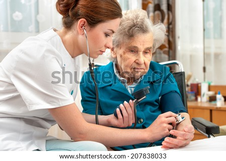 Female nurse measuring blood pressure of senior woman - stock photo