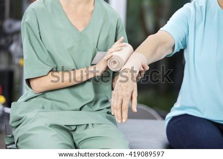 Female Nurse Putting Crepe Bandage On Senior Woman's Hand - stock photo