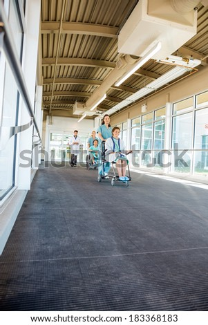 Female nurses pushing patients on wheelchairs while walking with doctor at corridor in hospital - stock photo