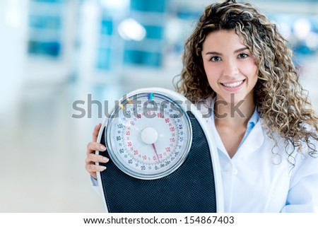 Female nutritionist at the hospital holding a weight scale  - stock photo