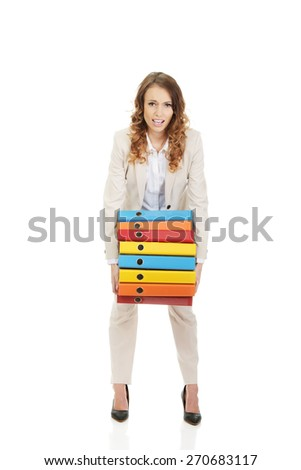 Female office worker carrying heavy binders. - stock photo