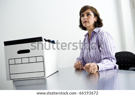 Female office worker, 40s, sitting at office table with cardboard file storage box - stock photo