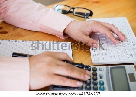 Female office worker typing on the keyboard and using a calculator to calculate the numbers - stock photo