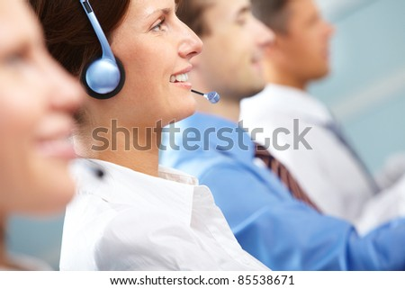 Female operator answering a call among her colleagues - stock photo