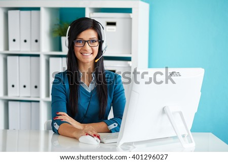 Female operator with headset smiling at camera in call center - stock photo