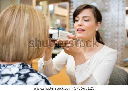 Female optometrist measuring pupilary distance on senior patient - stock photo