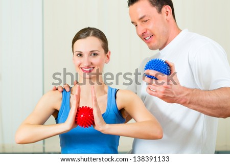 Female Patient at the physiotherapy doing physical exercises with her therapist, they using a massage ball - stock photo
