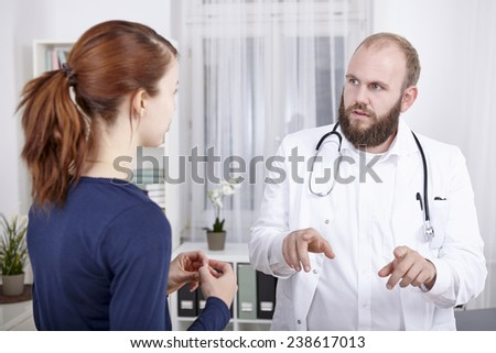 Female patient consulting doctor in practice - stock photo