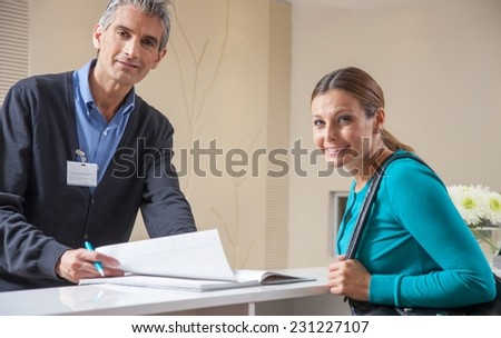 Female patient taking an appointment at the hospital reception. Health concept. - stock photo