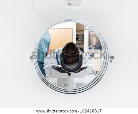 Female patient undergoing CT scan test in examination room - stock photo
