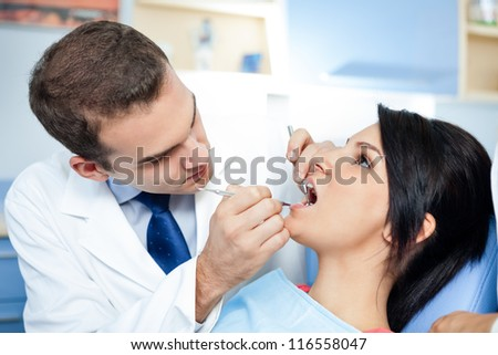 Female patient with dentist and assistant - dental treatment - stock photo