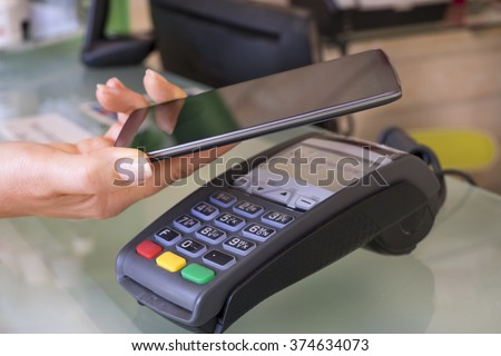 Female paying with NFC technology on smart phone, beautician, shop, market - stock photo
