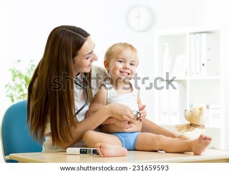 female pediatrician examining of child boy with stethoscope - stock photo