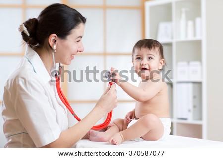 female pediatrician examining of toddler kid with stethoscope - stock photo