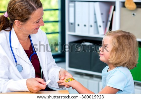 female pediatrician in white lab coat bandaging the hand of a little girl - stock photo