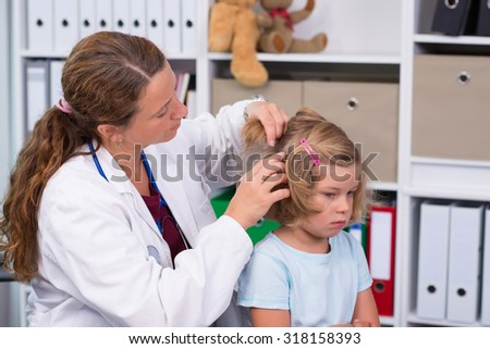 female pediatrician in white lab coat examined little girl - stock photo