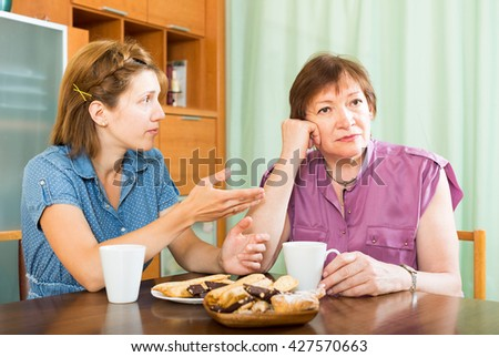 Female pensioner having conversation with her daughter during tea-drinking - stock photo
