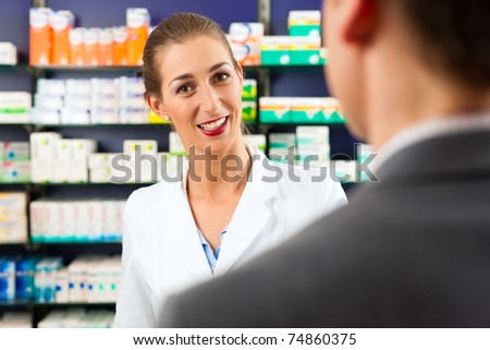 Female pharmacist consulting a customer in pharmacy - stock photo