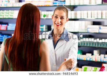 Female pharmacist consulting a female customer in her pharmacy - stock photo