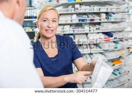 Female pharmacist explaining details of product to male customer in pharmacy - stock photo