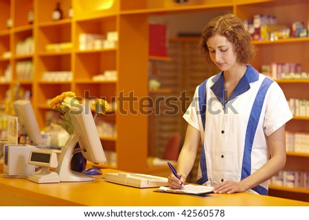 Female pharmacist filling out questionnaire in pharmacy - stock photo
