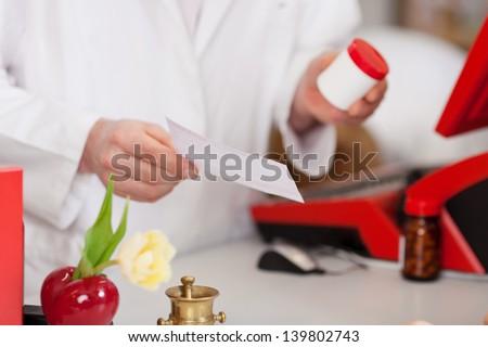 female pharmacist holding medicine bottle and prescription - stock photo