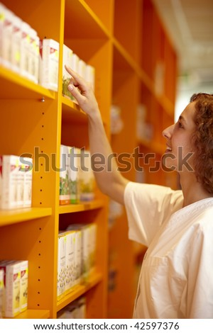 Female pharmacist looking for medicine in shelf - stock photo