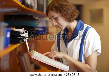 Female pharmacist reading in a red book - stock photo