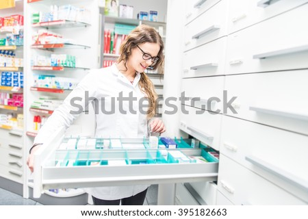 Female pharmacist taking a medicine from a shelf - Doctor opening a drawer in her pharmacy - stock photo