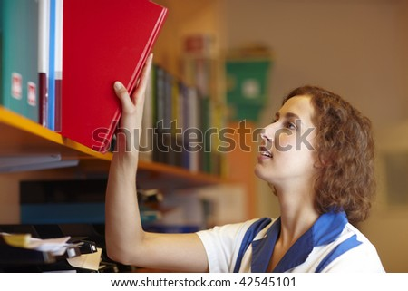 Female pharmacist taking red book from a shelf - stock photo