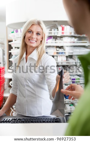 Female Pharmacist With Male Customer In Pharmacy Drugstore. - stock photo