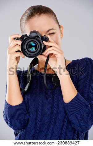 Female photographer taking a photo focusing the camera at the viewer as she composes her shot  over grey - stock photo