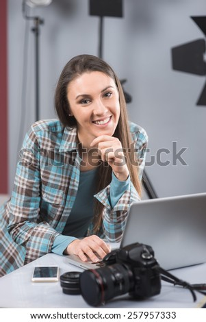 Female photographer working in her professional photo studio with a laptop, camera and lighting equipment - stock photo
