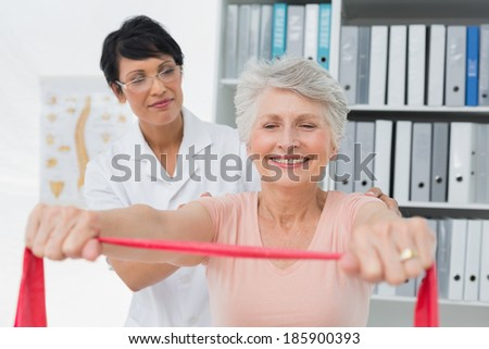 Female physiotherapist massaging senior womans back in the medical office - stock photo
