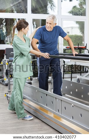 Female Physiotherapist Motivating Senior Man To Walk Between Par - stock photo