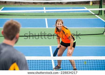 Female Pickleball player in action on an outside court - stock photo