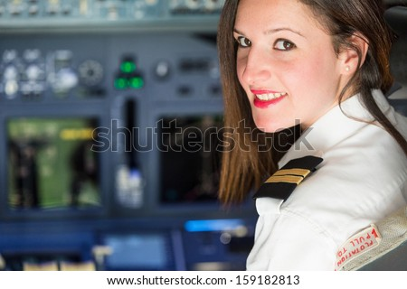 Female Pilot in the Airplane Cockpit - stock photo