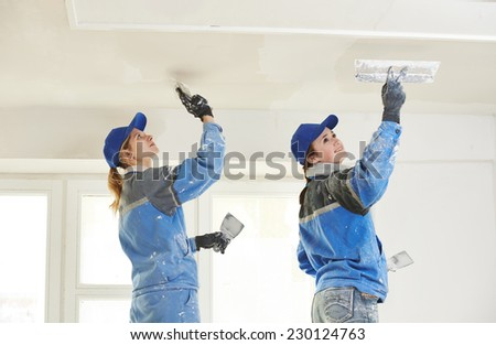 female plasterer painter at indoor ceiling renovation decoration stopping with spatula and plaster - stock photo
