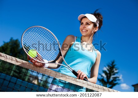 Female playing tennis on court - stock photo