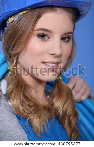 Female plumber carrying coiled pipe - stock photo