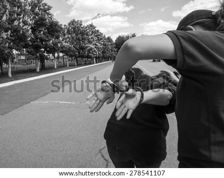 female police officer is handcuffed to a criminal - stock photo