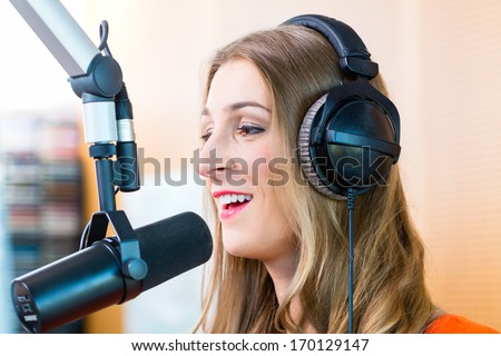 Female presenter or host in radio station hosting show for radio live in Studio - stock photo
