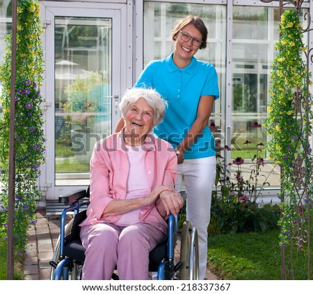 Female professional carer or middle-aged daughter behind happy elderly woman in wheelchair, in a green garden - stock photo
