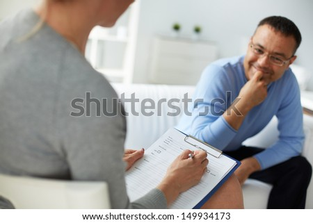 Female psychologist consulting mature man during psychological therapy session - stock photo