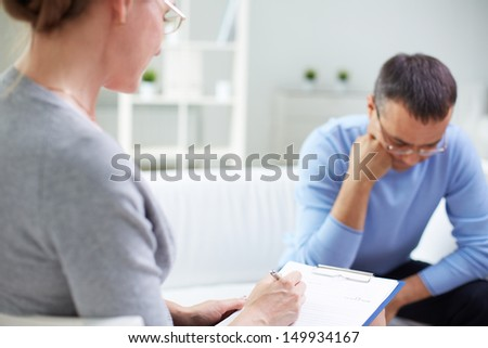 Female psychologist consulting pensive man during psychological therapy session - stock photo