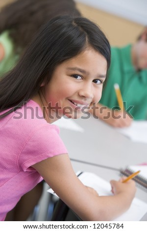 Female pupil in elementary school classroom writing - stock photo