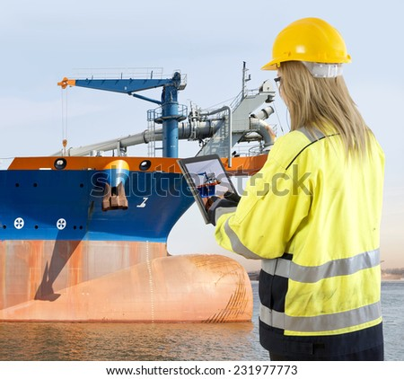 Female quality assurance manager takinga picture of a dredging vessel with her tablet, looking for specific details during an inspection round - stock photo